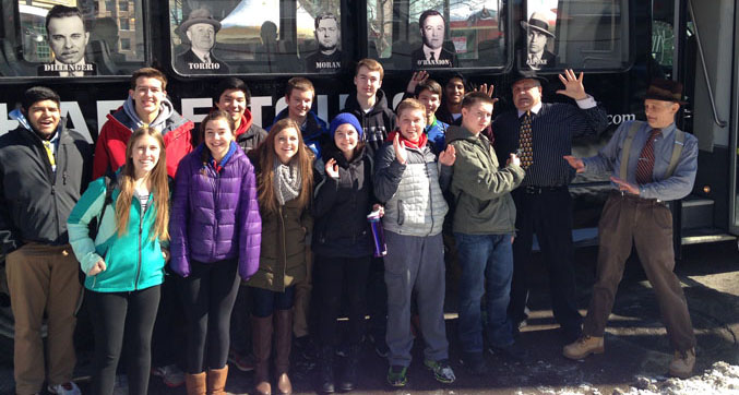 Social Studies club poses for a picture in front of their tour bus