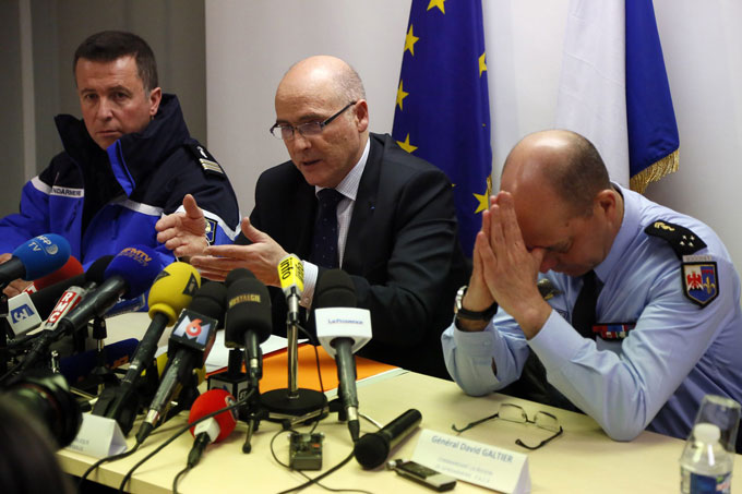 French prosecutor Brice Robin, center, discusses evidence pointing to deliberate actions by the co-pilot in the crash of a Germanwings jet, killing all 150 people on board, during a press conference on Thursday, March 26, 2015. Robin confirmed that Andreas Lubitz, a 28-year-old German citizen, refused to reopen the cockpit door for the pilot and pressed a button that sent the plane into its fatal descent.