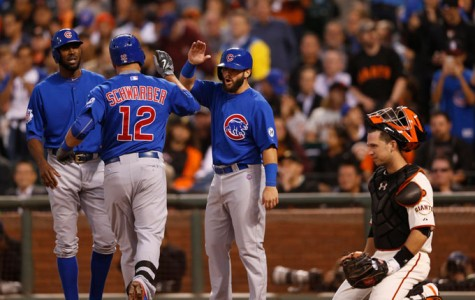 The Chicago Cubs' Kyle Schwarber (12) celebrates a three-run home run with teammates against the San Francisco Giants as catcher Buster Posey looks on in the third inning at AT&T Park in San Francisco on Tuesday, Aug. 25, 2015