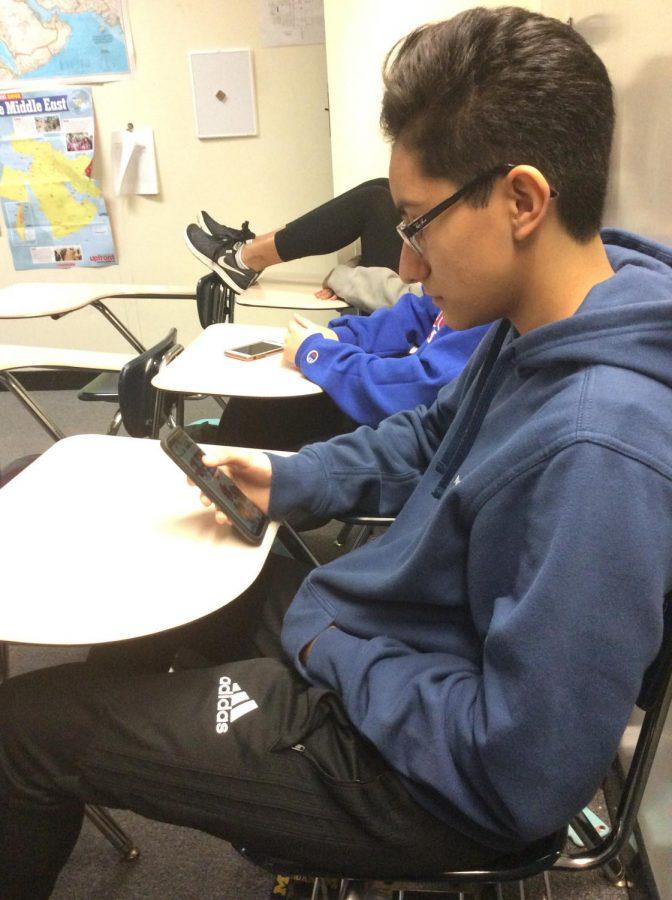 An AP Psych student checks her phone before class.