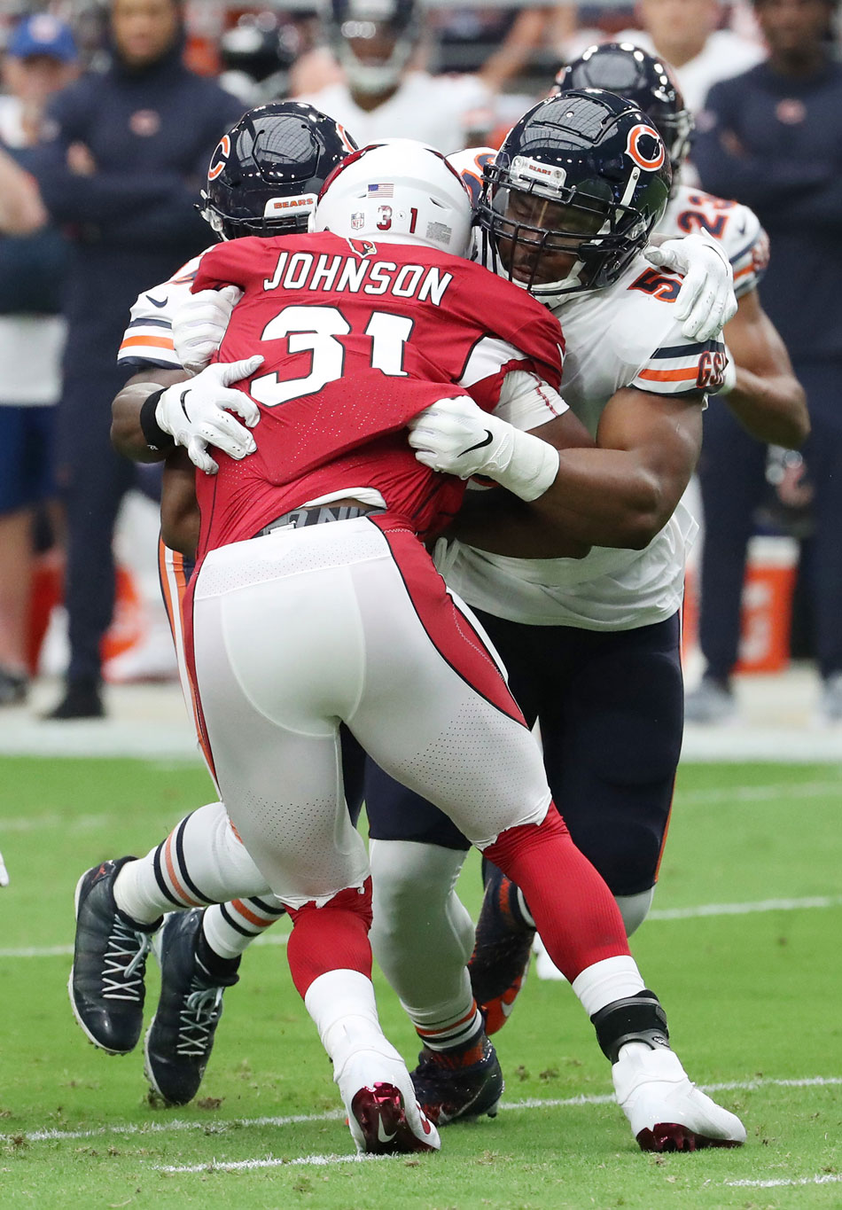 Chicago Bears linebackers Khalil Mack (52), right, and Danny Trevathan (59) tackle Arizona Cardinals running back David Johnson (31) in the first quarter on September 23, 2018, at State Farm Stadium in Glendale, Ariz.
