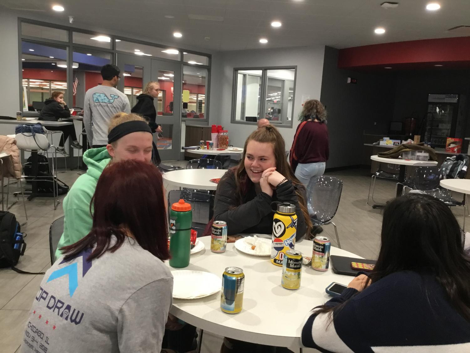 (From left) Jane Spencer, Haley Holz, Caroline Philbin, and Fidan Malikova talking at a Cutlass meeting.