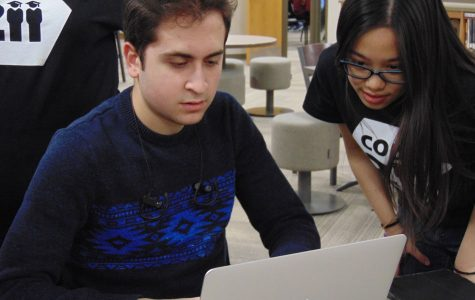 Besher Jabri (19) shows his new mobile app to fellow Palatine student Dominique De Fiesta (19).