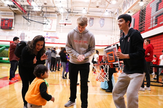 Palatine's basketball team plays with trick or treaters during the annual PHS Hallween festival.