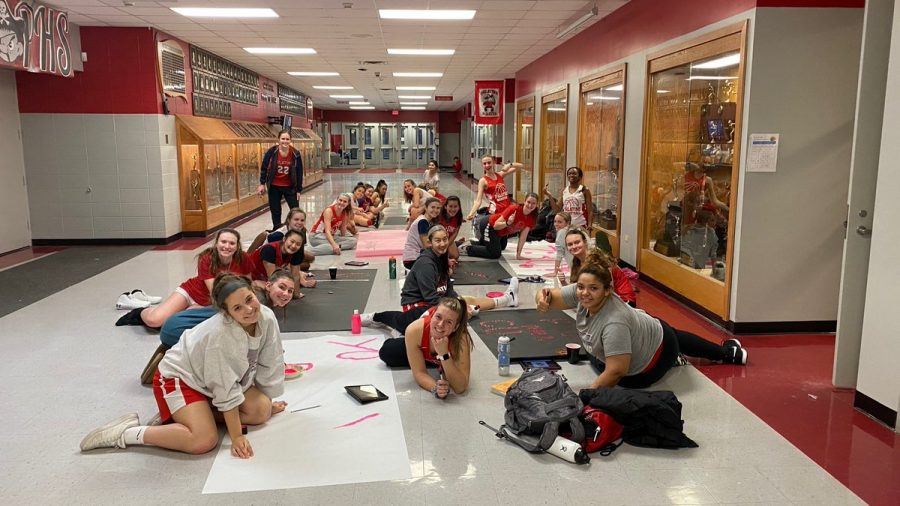 PHS Girls Basketball make signs to hand around the gyms for Breast Cancer Awareness Night.