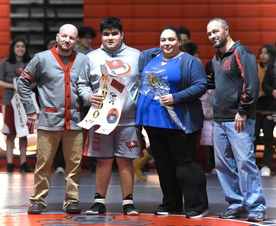 Mando Hernandez stands with his coaches and family at Seniors Night.