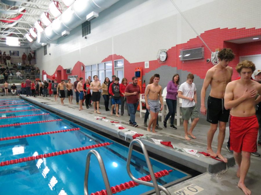 PHS Parents and family members walk with the senior swimmers and divers.