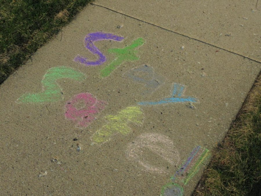 Reminders for people to stay healthy and happy spread across a sidewalk.