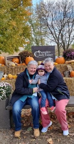 Dawn Shepherd (left) sits with her wife and her granddaughter at Pumpkin Creek Farms in Sherman, IL.