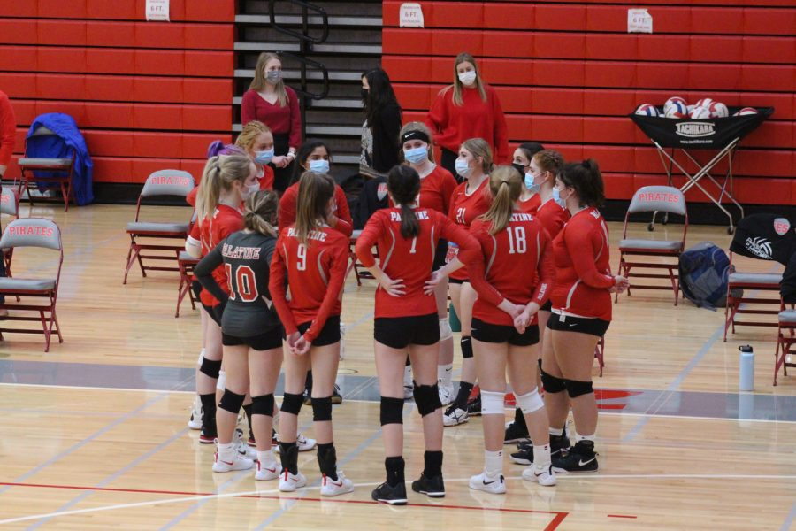 The girls varsity volleyball team talks strategy during a timeout.