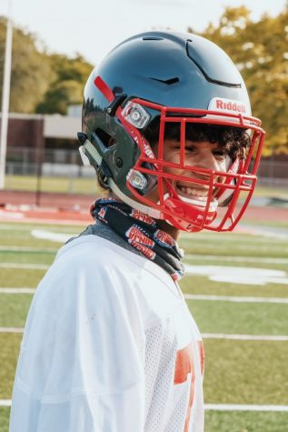 Freshman at Palatine High School, Dominik Ball, laughing on the field as he heads onto his next drill with the varsity football team.