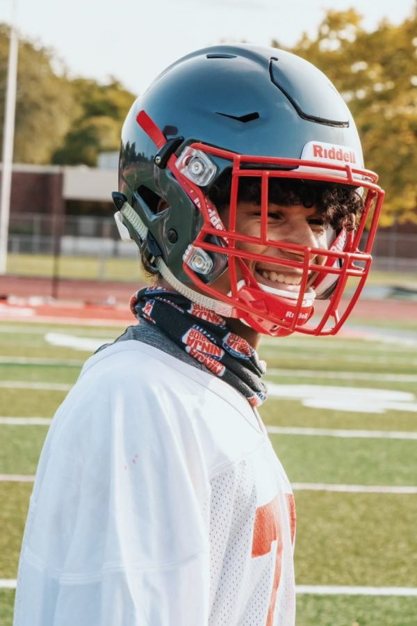 Freshman+at+Palatine+High+School%2C+Dominik+Ball%2C+laughing+on+the+field+as+he+heads+onto+his+next+drill+with+the+varsity+football+team.