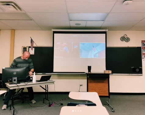 English teacher Sean Berleman takes attendance for students in person and Zoom.