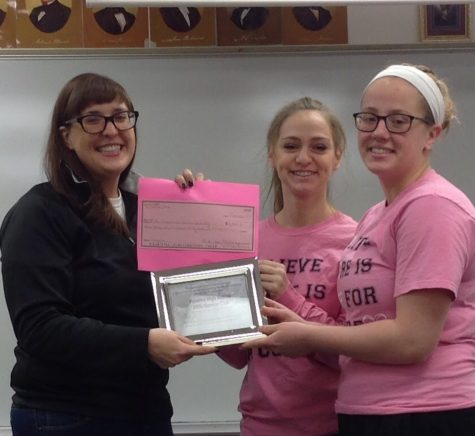 Three pink-out supporters holding up a check for $3,000 to be donated to research into cures for breast cancer