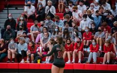 """Junior Brianna Squeo serves in front of the student section. The students came out in full support against PHS's crosstown rival. The theme was """"whiteout""""."""